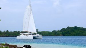 Catamaran sailing boat in the San Blas islands with clear blue water